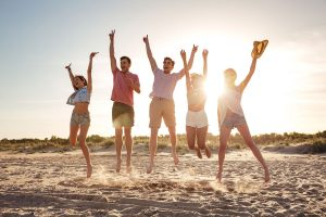 Group of happy young friends dressed in summer clothes jumping together with hands raised at he beach