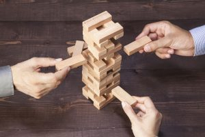 Businessmen Hands Playing Wooden Tower Game on Top of  Wooden Table. Teamwork, Strategy and Vision.