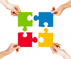 business, teamwork and collaboration concept - four hands connecting colorful puzzle pieces