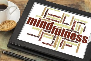 mindfulness word cloud on a digital tablet against a grunge wood table with a cup of coffee