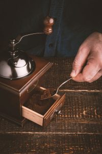 Man making coffee with coffee mill vertical