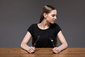 Girl holding cutlery, sitting beside empty table, dark background.