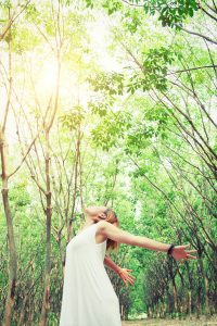 women lifestyle concept : young asian woman stretch her hands in fresh air look so comfortable in the forest