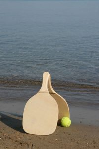 two wooden beach rackets by the shore with yellow ball