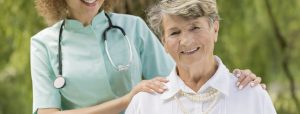 Smiling senior female patient and her nurse outdoor
