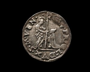 Ancient silver Venetian coin isolated on black, macro shot
