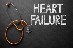 Medical Concept: Heart Failure Handwritten on Black Chalkboard. Top View of Orange Stethoscope on Chalkboard. Medical Concept: Heart Failure on Black Chalkboard. 3D Rendering.