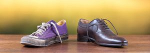Old used purple sneaker next to luxury brown shoe on blurred background