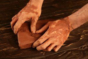 artist man hands working red clay to create handcraft art
