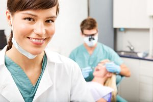 A portrait of a dental assistant smiling at the camera with the dentist working in the background