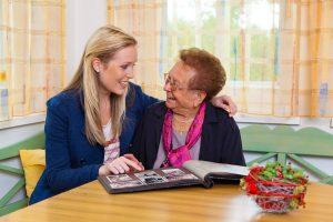 Ein Enkel besucht seine Großmutter. Ansehen des Fotoalbums.