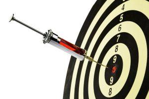 Die Spritze eines Arztes in der Mitte einer Zielscheibe. Injektion mit Blut.