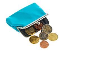 Eine leere Geldbörse mit wenigen Euromünzen. Symbolphoto für Schulden und Armut