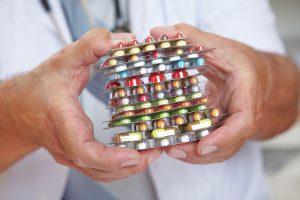 Viele bunte Tabletten gehalten von den Händen eines Arztes