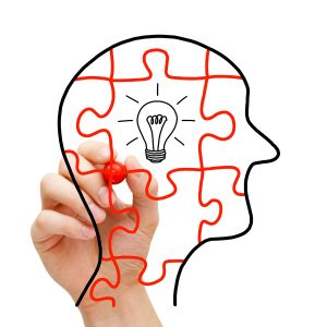 Creative thinking concept. Puzzle human head with glowing light bulb in the middle.