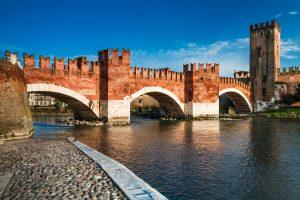 View of Adige river and medieval stone bridge of Ponte Scaligero in Verona, built in 14th century near Castelvecchio. Italy.