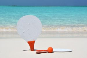 Two rackets and a ball on the sandy beach
