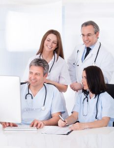 Female And Male Doctors Looking At Computer In Clinic