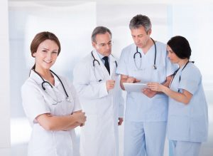 Female Doctor Standing In Front Of Team Using Digital Tablet