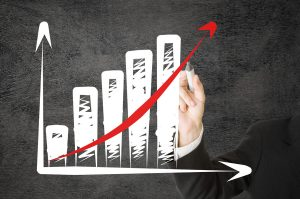 Businessman drawing rising graph with red arrow - success or strategy concept