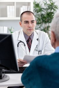 Handsome doctor with patient at office