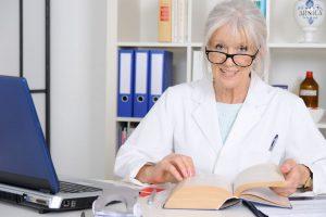 Senior Ärztin schlägt im Fachbuch nach