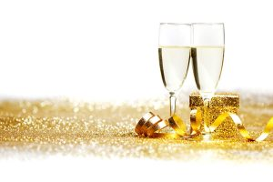 Two champagne glasses and gifts on golden background