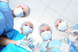 View from below of surgeons in protective work wear during operation