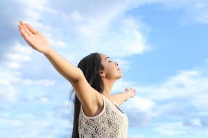 Portrait of a beautiful arab woman breathing fresh air with raised arms with a cloudy blue sky in the background