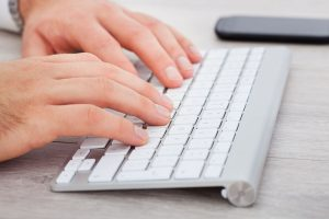 Close-up Of Male Hand Typing On Keyboard