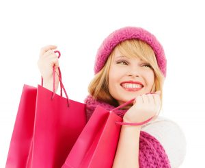 winter, people and happiness concept - woman in pink hat and scarf with many shopping bags