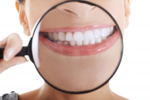 Beautiful woman with magnifying glass showing her perfect white teeth. Over white background.