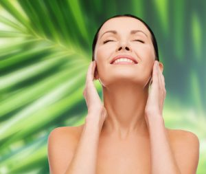 health, spa and beauty concept - clean face and hands of beautiful smiling woman with closed eyes