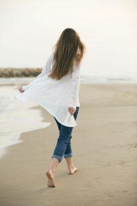 girl walking alone on the beach shore