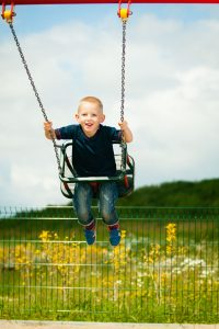 Little blonde boy having fun at the playground. Child kid playing on a swing outdoor. Happy active childhood.
