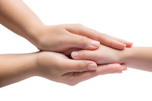 Hand of woman touching her son isolated on white background