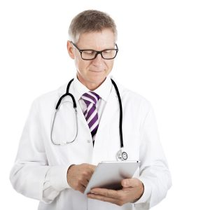 Doctor checking patient notes on a tablet-pc standing with his stethoscope around his neck reading the information on the screen, isolated on white