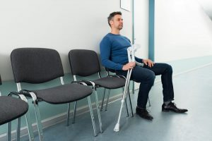 Mid-adult Man Sitting On Chair With Crutches In Hospital