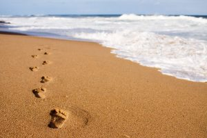 Human footprints leading away from the viewer into the sea